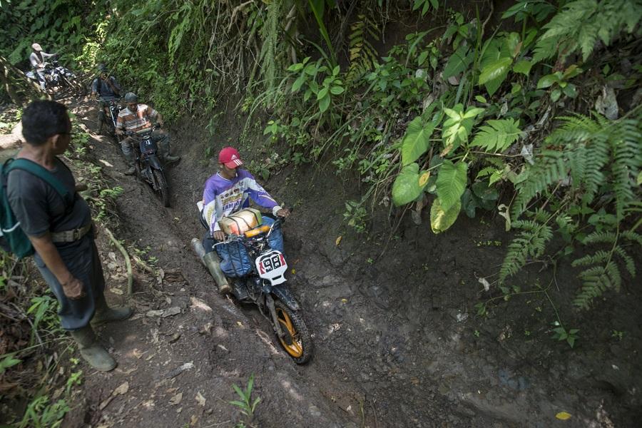 Para petani HKm Pala Makmur menembus setapak sempit, dalam dan licin dengan mengendarai sepeda motor gurandong. Foto oleh Agus Prijono