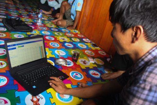 Seorang kader database sedang menjelaskan sistem database desa.